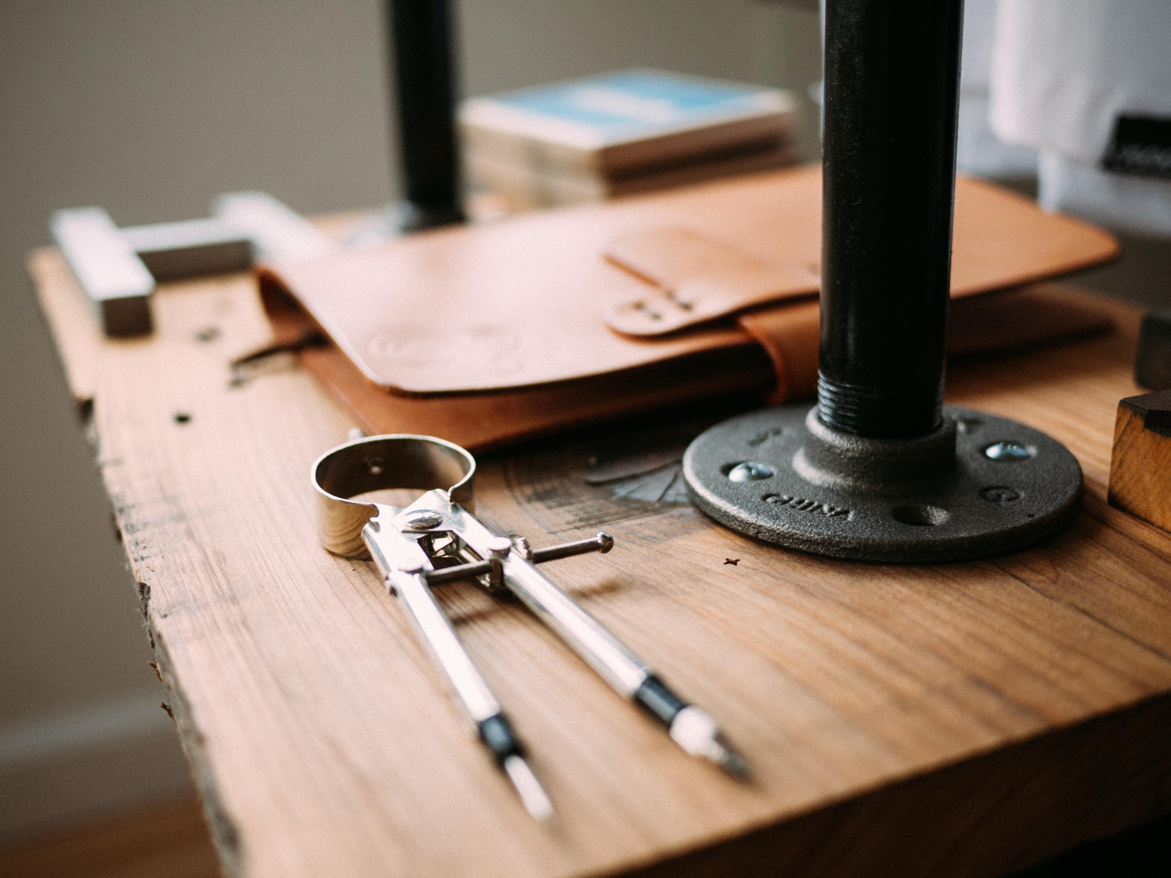 Schreibtisch mit Zirkel und Mappe